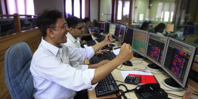 MUMBAI, INDIA - MAY 13: Stock traders rejoice the as Sensex rose to a third consecutive record high at Bombay stock exchange on May 13, 2014 in Mumbai, India. The Sensex hit a record high of 24,068.94, surpassing the psychologically important 24,000 mark for the first time in its history surging after exit polls showed the Bharatiya Janata Party and its allies winning a majority in the elections. (Photo by Anshuman Poyrekar/Hindustan Times via Getty Images)
