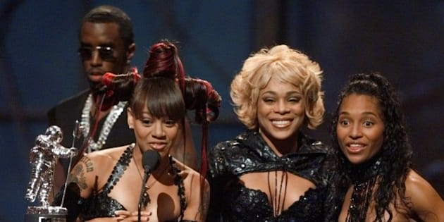 "Left Eye, second left, T-Boz, center, and Chili, right, of the group TLC accept their award for best group video for their song ""No Scrubs,""  Thursday, Sept. 9, 1999, as Sean ""Puffy"" Combs looks on from behind, at the 1999 MTV Video Awards in New York. (AP Photo/Ron Frehm)"