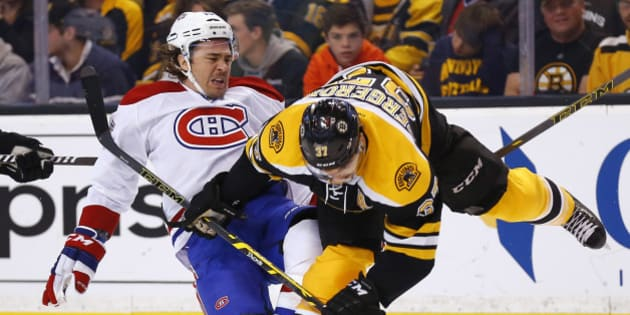 Montreal Canadiens' P.A. Parenteau, left, is checked by Boston Bruins' Patrice Bergeron during the first period of an NHL hockey game in Boston, Saturday, Nov. 22, 2014. (AP Photo/Winslow Townson)