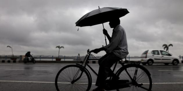 An Indian man keeps himself from rain with an umbrella while riding a bicycle in Hyderabad, India, Friday, Oct. 25, 2013. Heavy rains triggered by northeast monsoon have lashed several parts of Andhra Pradesh state for the fourth consecutive day today prompting authorities to evacuate many of from low-lying areas, according to local reports. (AP Photo/Mahesh Kumar A.)