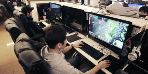 "Shin Minchul, bottom, a 21-year-old college student, plays online computer games at an Internet cafe in Seoul, South Korea, Wednesday, Dec. 11, 2013. A law under consideration in South Korea's parliament has sparked vociferous debate by grouping popular online games such as ""StarCraft"" with gambling, drugs and alcohol as an anti-social addiction the government should do more to stamp out.(AP Photo/Ahn Young-joon)"
