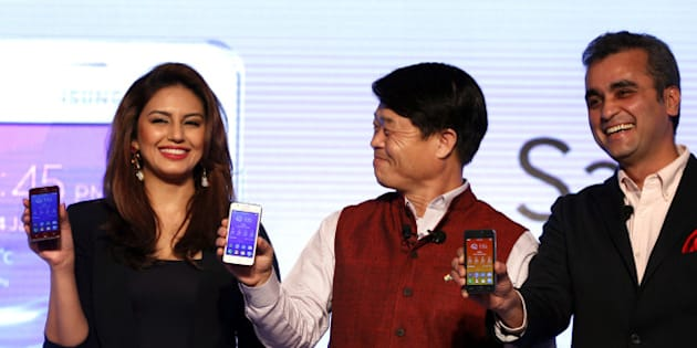 NEW DELHI, INDIA - JANUARY 14: Actress Huma Qureshi with Samsung CEO Hyun Chil Hong and Vice -President of the company Asim Warsi at the launch of Samsung Z1 on January 14, 2015 in New Delhi, India.  Samsung launched here the first smartphone powered by its own Tizen operating system to rival Googles dominant Android platform - making India the first country for this global launch. Samsung Z1 with 3G capability and a liquid-crystal display is priced at Rs 5,700 and targets first-time smartphone buyers. (Photo by Ajay Aggarwal/Hindustan Times via Getty Images)