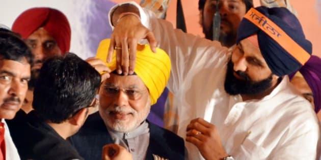 AMRITSAR, INDIA - APRIL 25: Punjab Cabinet Minister Bikram Singh Majithia tying turban on BJP Prime Ministerial candidate Narendra Modi during an election campaign rally in favour of BJP Lok Sabha Candidate from Amritsar Arun Jaitley on April 25, 2014 in Amritsar, India. Addressing five election rallies in Pathankot, Hoshiarpur, Ludhiana, Bathinda and Amritsar cities of Punjab Friday in favour of the Shiromani Akali Dal (SAD)-Bharatiya Janata Party (BJP) combine candidates, Modi said the electorate has bid farewell to the United Progressive Alliance (UPA) government already. (Photo by Sameer Sehgal/Hindustan Times via Getty Images)