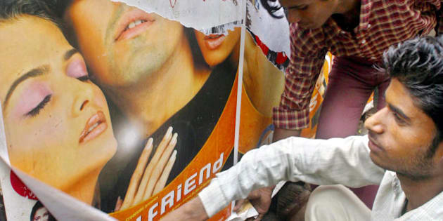 """Two movie theater workers remove a poster of Bollywood film """"Girlfriend"""" in Allahabad, India, Tuesday, June 15, 2004.  Hindu hard-liners smashed glass panes and ripped posters in movie theaters, then said on Wednesday they'd pressure the government to censor or ban the film about a lesbian couple. (AP Photo/Rajesh Kumar Singh)"""