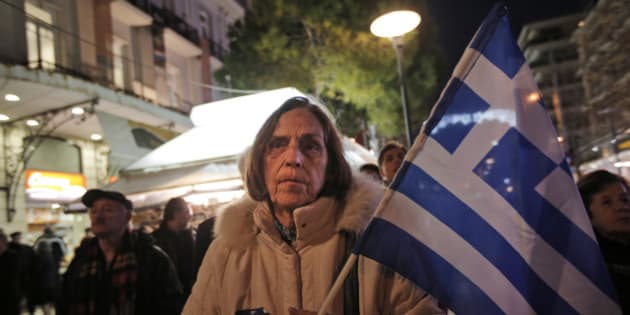A supporter of Greece's conservative New Democracy party, holding the national flag, waits to greet the party's leader and Prime Minister Antonis Samaras, during a visit in Athens, Tuesday, Jan. 20, 2015. Samaras' party has failed so far to overcome a gap in opinion polls with the anti-bailout Syriza party ahead of the Jan. 25 general election. Weekend opinion polls showed New Democracy party trailing the anti-bailout Syriza party in voter support and that a coalition government is likely to emerge from Sunday's vote. (AP Photo/Lefteris Pitarakis)