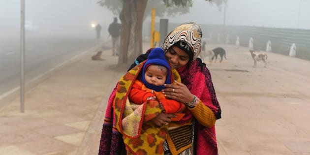 An Indian woman carries her child covered with blankets on a foggy winter morning in New Delhi on January 8, 2015. Bone-chilling temperatures have gripped northern India with foggy conditions frequently disrupting rail, road and air traffic. AFP PHOTO / CHANDAN KHANNA        (Photo credit should read Chandan Khanna/AFP/Getty Images)