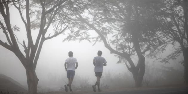 People jog on a foggy cold morning in Hyderabad, India, Sunday, Jan. 8, 2012. Though India is famous for its brutally hot summers, temperatures fall sharply for a few weeks in December and January. (AP Photo/Mahesh Kumar A)