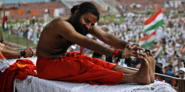 Indian yoga guru Baba Ramdev stretches during an anti-corruption protest in New Delhi, India, Tuesday, Aug. 14, 2012. Ramdev sipped a glass of fruit juice offered by supporters ending his hunger strike Tuesday but said his battle against endemic corruption in India will continue. (AP Photo/Rajesh Kumar Singh)