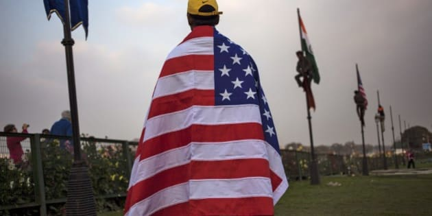 An Indian worker wears an American flag before it is hoisted up a flag pole in New Delhi, India, Friday, Jan. 23, 2015. India's Prime Minister Narendra Modi has invited U.S. President Barack Obama to be the first American president to attend India's annual Republic Day festivities marked on Jan. 26. (AP Photo/Tsering Topgyal)