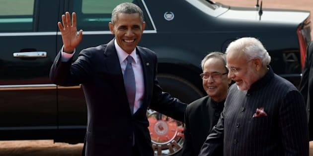 US President Barack Obama (L) waves as Indian President Pranab Mukherjee (C) and Indian Prime Minister Narendra Modi (R) look on as he leaves following a welcome ceremony at the Presidential Palace in New Delhi on January 25, 2015. US President Barack Obama began a landmark visit to India on January 25 with a bear hug from Prime Minister Narendra Modi, signalling a new warmth in a sometimes strained relationship. AFP PHOTO/Roberto SCHMIDT        (Photo credit should read ROBERTO SCHMIDT/AFP/Getty Images)