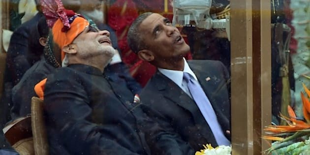 Indian Prime Minister Narendra Modi (L) talks with US President Barack Obama (R) while watching the fly-past during India's Republic Day parade on Rajpath in New Delhi on January 26, 2015. Rain failed to dampen spirits at India's Republic Day parade January 26 as Barack Obama became the first US president to attend the spectacular military and cultural display in a mark of the nations' growing closeness. AFP PHOTO/ PRAKASH SINGH        (Photo credit should read PRAKASH SINGH/AFP/Getty Images)