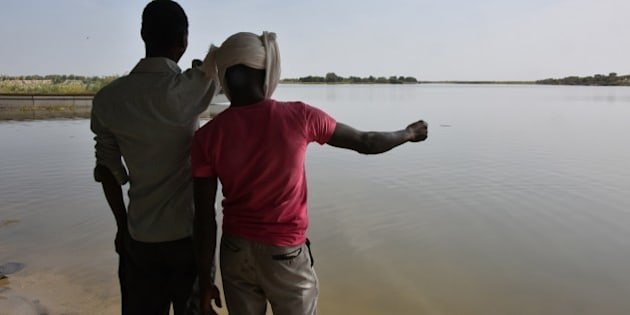 A survivor of a Boko Haram's attack and his friend look at the waters of  Lake Chad which borders Chad, Nigeria, Niger and Cameroon, in Bol on January 25, 2015. Chad's President Idriss Deby has secured control of regional operations against Boko Haram Islamists, riding roughshod over his supposed allies in a week-long diplomatic and military offensive.  There have been months of disagreements between the countries directly threatened by Boko Haram -- Nigeria, Cameroon, Chad and Niger -- on exactly how to take on the Islamists.  AFP PHOTO / SIA KAMBOU        (Photo credit should read SIA KAMBOU/AFP/Getty Images)