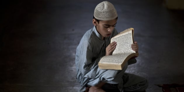 A Pakistani student of a madrassa, or Islamic school, attends a test in reciting verses of the Quran, during the Muslim holy fasting month of Ramadan, in a Mosque in Islamabad on Monday, July 22, 2013. Muslims throughout the world are marking the month of Ramadan, the holiest month in Islamic calendar. (AP Photo/Muhammed Muheisen)