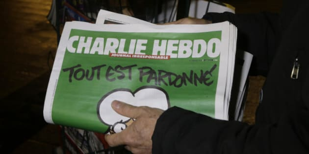 """A seller of newspapers installs in shelf, several Charlie Hebdo newspapers at a newsstand in Nice southeastern France, Wednesday, Jan. 14, 2015. On front page reading """"All is forgiven"""". Charlie Hebdo's defiant issue is in print, with a caricature of the Prophet Muhammad on the cover and a double-page spread claiming that more turned out Sunday to back the satirical weekly """"than for Mass."""" Twelve people died when two masked gunmen assaulted the newspaper's offices on Jan. 7, including much of the editorial staff and two police. (AP Photo/ Lionel Cironneau)"""
