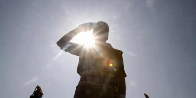 A Jammu and Kashmir state police officer salutes during a function to mark Police Commemoration Day, on the outskirts of Srinagar, India, Monday, Oct. 21, 2013. The annual Police Commemoration Day is being observed Monday to remember and pay respect to fallen policemen in the troubled Kashmir region. More than a dozen militant groups have been fighting since 1989 seeking independence for Kashmir or its merger with neighboring Pakistan, where at least 68,000 people, most of them civilians, have died in the 24th year of conflict. (AP Photo/Mukhtar Khan)