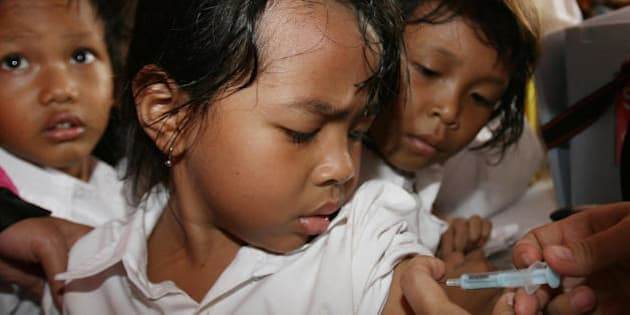 JAKARTA, INDONESIA: Children look as a young girl gets vaccinated in Jakarta, 27 February 2007. IndonesiaIndonesia has launched a campaign to vaccinate 14 million children against measles. The campaign is supported by UNICEF, the American Red Cross and the World Health Organisation. AFP PHOTO/AHMAD (Photo credit should read AHMAD/AFP/Getty Images)