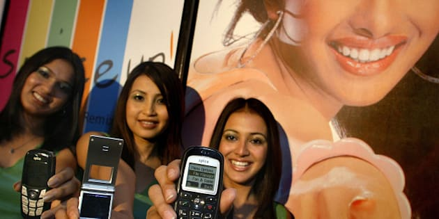 Models pose with Spice mobile handsets at the launch of the product in New Delhi, India, Tuesday, June 7, 2005. The handsets are priced from INR 2500 (US$ 58) upwards. In the background is the poster of Bollywood actress and brand ambassador Priyanka Chopra. (AP Photo/Gurinder Osan)