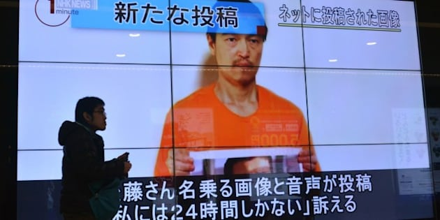 A pedestrian looks at a large screen in Tokyo on January 28, 2015 showing television news reports about Japanese hostage Kenji Goto who has been kidnapped by the Islamic State group. Japan has asked Jordan for help after the Islamic State jihadist group threatened to kill a Japanese journalist and a Jordanian pilot within 24 hours unless Amman frees a jailed female militant.    AFP PHOTO / KAZUHIRO NOGI        (Photo credit should read KAZUHIRO NOGI/AFP/Getty Images)