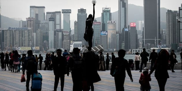 People walk on Victoria harbor waterfront in Hong Kong on January 28, 2015.  According to local reports citing the US think tank Heritage Foundation, Hong Kong has been ranked the worlds freest economy for the 21st year in a row but is weighed down by perceived corruption and eroding public trust.  AFP PHOTO / Philippe Lopez        (Photo credit should read PHILIPPE LOPEZ/AFP/Getty Images)