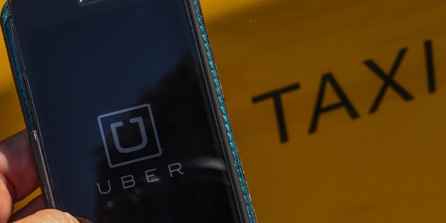 BARCELONA, SPAIN - JULY 01:  In this photo illustration, the new smart phone app 'Uber' logo is displayed on a mobile phone next to a taxi on July 1, 2014 in Barcelona, Spain. Taxi drivers in main cities strike over unlicensed car-halling services. Drivers say that is a lack of regulation behind the new app.  (Photo Illustration by David Ramos/Getty Images)