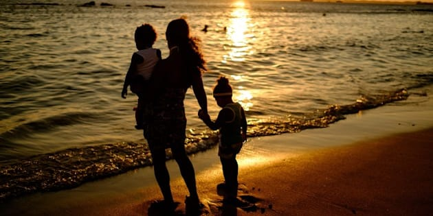 A mother and her children watch the sunset at Boa Viagem beach in Salvador, Brazil, on December 31, 2014. AFP PHOTO / YASUYOSHI CHIBA        (Photo credit should read YASUYOSHI CHIBA/AFP/Getty Images)