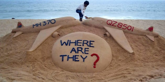 Indian sand artist Sudarsan Pattnaik gives the final touches to his sand sculpture portraying two missing aircraft, Air Asia QZ8501 and Malayasia Airlines MH370 on Golden Sea Beach at Puri, some 65 kms east of Bhubaneswar on December 29, 2014.  An AirAsia Airbus plane with 162 people on board went missing en route from Surabaya in Indonesia to Singapore early on December 28, officials and the airline said, in the third major incident to affect a Malaysian carrier this year.   AFP PHOTO/STR        (Photo credit should read STRDEL/AFP/Getty Images)