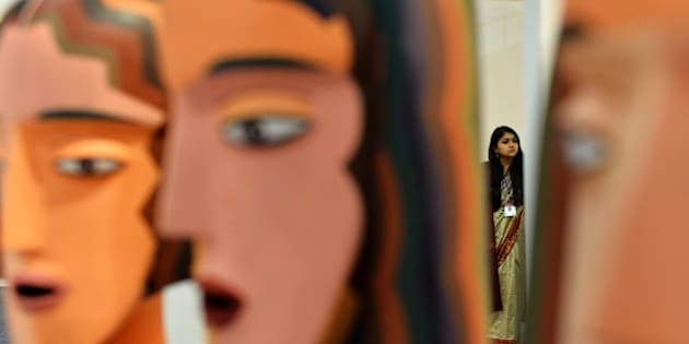 In this photograph taken on January 29, 2015 an Indian woman looks on during the India Art Fair in New Delhi.   For years, its been Indias grand art festival but this year more than ever, India Art Fair is raking more eyes balls by bringing a gamut of modern and contemporary works from across the world to satiate the growing art appetite of the metropolis - Delhi.   AFP PHOTO / CHANDAN KHANNA        (Photo credit should read Chandan Khanna/AFP/Getty Images)