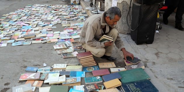 In this Friday, Jan. 23, 2015 photo, an Iraqi man looks at books on al-Mutanabi Street, home to the city's book market in central Baghdad. One afternoon this month, Islamic State militants arrived at the Central Library of the northern city of Mosul in a non-combat mission. They broke the locks that kept the two-story building closed since the extremists overran the city in mid last year, loading some 2,000 books included children stories, poetry, philosophy, sports, health and cultural and scientific publications into six pickup trucks and leaving behind only the Islamic religious ones. (AP Photo/Karim Kadim)