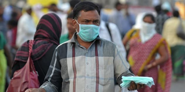 An Indian vendor sells face masks for swine flu prevention outside a railway station in Secunderabad on January 27, 2015. Twenty two swine flu deaths have been recorded since January with more than 440 positive cases in the southern Indian state of Telangana, according to a report. AFP PHOTO / Noah SEELAM        (Photo credit should read NOAH SEELAM/AFP/Getty Images)