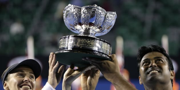 Martina Hingis of Switzerland, left,  and Leander Paes of India lift the trophy after defeating Kristina Mladenovic of France and Daniel Nestor of Canada in the mixed doubles final at the Australian Open tennis championship in Melbourne, Australia, Sunday, Feb. 1, 2015. (AP Photo/Bernat Armangue)