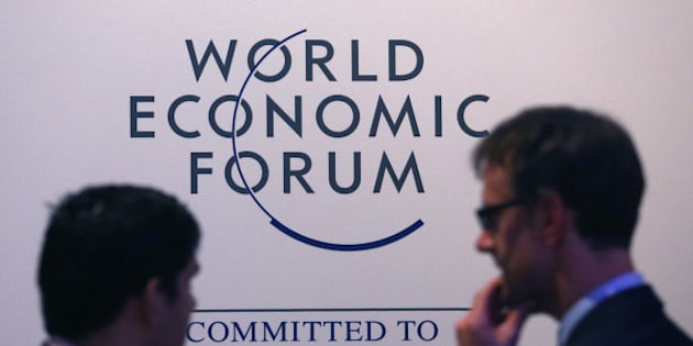 Attendees pass a World Economic Forum logo as they walk through the Kongress Zentrum, or Congress Center, during a break in sessions on day three of the World Economic Forum (WEF) in Davos, Switzerland, on Friday, Jan. 23, 2015. World leaders, influential executives, bankers and policy makers attend the 45th annual meeting of the World Economic Forum in Davos from Jan. 21-24. Photographer: Chris Ratcliffe/Bloomberg via Getty Images