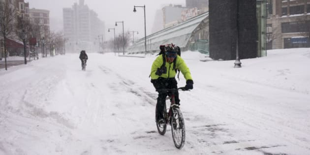 BOSTON, MA - JANUARY 27: Two bicyclists travel over snow January 27, 2015 along an empty Commonwealth Avenue in Boston, Massachusetts. Public transportation in Boston has been shut down due to a heavy snow storm with blizzard conditions set to leave over two feet of snow. (Photo by Robert Nickelsberg/Getty Images)