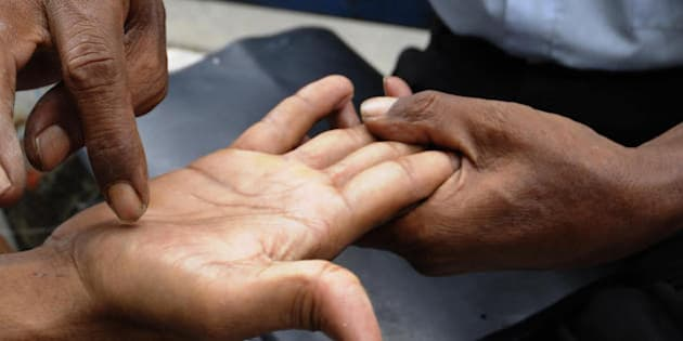A Bangladeshi astrologer reads the palm of a client on a pavement in Dhaka on May 28, 2009.    Bangladesh is one of the poorest nations on the planet with some 40 percent of its 144 million people living on less than one US dollar a day.     AFP PHOTO/Munir uz ZAMAN (Photo credit should read MUNIR UZ ZAMAN/AFP/Getty Images)