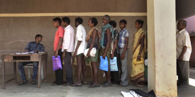 In this Wednesday, March 21, 2012 photo, Sukhbasi Mandani, 50, second from right, stands in a line with others to buy subsidized rice from a fair price shop in the Public Distribution System in Rayagada, in Indian eastern state of Orissa. India's Public Distribution System sends out 45 million metric tons of heavily subsidized food each year to help 400 million people in their tenuous struggle for survival, but in reality, the $15 billion national program is riven with corruption. But new devices are transforming Rayagada into a laboratory to test a thesis with deep implications for the future of India: Can technology fix a nation? (AP Photo/Manish Swarup)