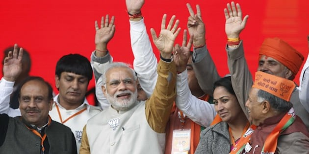 NEW DELHI, INDIA - FEBRUARY 3: Prime Minister Narendra Modi waves alongside Bharatiya Janata Party (BJP) members during a public rally for the upcoming Delhi Assembly Elections, on February 3, 2015 in New Delhi, India. Modi launches an all-out frontal attack on AAP, says those who knew who have accounts in Swiss banks, who kept such names in their pockets, are now saying we don't know who gave us money. He mocks at Aam Aadmi Party, calls it a 'temporary party'. He promises abundant power supply in the national capital. (Photo by Virendra Singh Gosain/Hindustan Times via Getty Images)