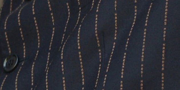 This photograph taken on January 25, 2015, shows detail on Indian Prime Minister Narendra Modi's suit bearing his own name during a joint press conference after delegation level talks with US President Barack Obama in New Delhi. Narendra Modi's daring fashion choices have won plaudits in the past, but the Indian leader's decision to wear a suit with his own name printed all over it sparked a barrage of mockery on social media. AFP PHOTO / PRAKASH SINGH        (Photo credit should read PRAKASH SINGH/AFP/Getty Images)