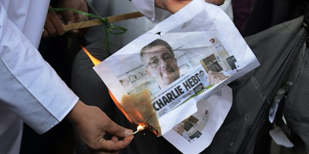 Indian Muslim activists from the Majlis Bachao Tahreek (MBT) burn an image depicting former publishing director of the French magazine Charlie Hebdo, Stephane Charbonnier, who was killed by gunmen during an attack on the magazine's office, during a protest in Hyderabad on January 16, 2015. Muslims have staged angry protests over magazine Charlie Hebdo's decision to depict the Prophet Mohammed on its latest front cover. AFP PHOTO / Noah SEELAM        (Photo credit should read NOAH SEELAM/AFP/Getty Images)