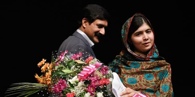 Pakistani rights activist Malala Yousafzai, stands with her father Ziauddin Yousafzai as she holds bouquets of flowers after addressing the media in Birmingham, central England on October 10, 2014. The Nobel Peace Prize went Friday to 17-year-old Pakistani Malala Yousafzai and India's Kailash Satyarthi for their work promoting children's rights. Seventeen-year-old Nobel Peace Prize winner Malala Yousafzai said she was 'honoured' to be the first Pakistani and the youngest person to be given the award and dedicated the award to the 'voiceless'. 'This award is for all those children who are voiceless, whose voices need to be heard,' she said. AFP PHOTO / OLI SCARFF        (Photo credit should read OLI SCARFF/AFP/Getty Images)