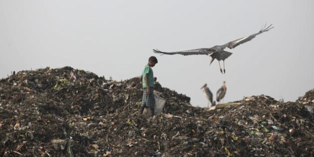 An Indian child looks for recyclable material at a garbage dumping site on the outskirts of Gauhati, India, Monday, Jan. 26, 2015. The White House is hoping that the surprise deal with China late last year setting ambitious targets for cutting greenhouse gas emissions will influence India and others. Heavy reliance on fossil fuels has transformed New Delhi into the planet's most polluted capital and made India the third biggest national emitter of greenhouse gases. (AP Photo/Anupam Nath)