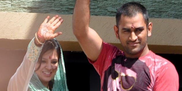 Newly-weds Mahendra Singh Dhoni, Indian cricket team captain, and Sakshi greet fans from the balcony of a family home in Ranchi on JUly 7, 2010. Dhoni and Sakshi married in a hush-hush ceremony on July 4 at a farmhouse near Dehradun. AFP PHOTO/STR (Photo credit should read STRDEL/AFP/Getty Images)