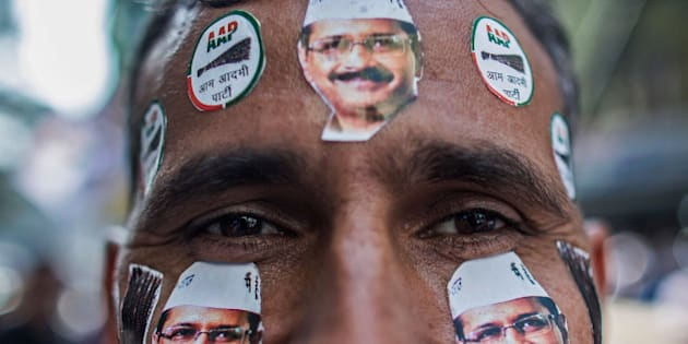 DELHI, INDIA - FEBRUARY 10:  A man is seen with Aam Aadmi Party (AAP) leader Arvind Kejriwal stickers on his face as he watches the results of Delhi Assembly Elections at the party Patel Nagar Office on February 10, 2015 in Delhi, India. Arvind Kejriwal and his AAP party have taken victory in Delhi's state elections which will see Kejriwal return for a second time as Delhi's chief minister.  (Photo by Lam Yik Fei/Getty Images)