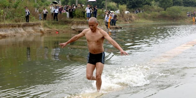 QUANZHOU, CHINA - OCTOBER 26:  (CHINA OUT) Shi Liliang, a monk of Shaolin Temple, runs on plywoods which float on water on October 26, 2014 in Quanzhou, Fujian province of China. Shi Liliang, a monk of Shaolin Temple, perfromed water run and broke his record of 100 meters with 118 meters on Sunday.  (Photo by ChinaFotoPress/ChinaFotoPress via Getty Images)