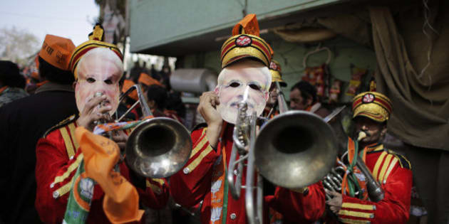 Members of a brass band wear masks of Indian Prime Minister Narendra Modi during an election campaign rally for India's ruling Bharatiya Janata Party (BJP) for the upcoming Delhi state election in New Delhi, India, Thursday, Feb. 5, 2015. Delhi goes to the polls on Feb. 7. (AP Photo/Altaf Qadri)