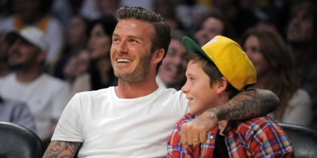 Soccer star David Beckham sits with his son Brooklyn as they watch the Los Angeles Lakers play the Miami Heat in their NBA basketball game, Sunday, March 4, 2012, in Los Angeles. The Lakers won 93-83.  (AP Photo/Mark J. Terrill)