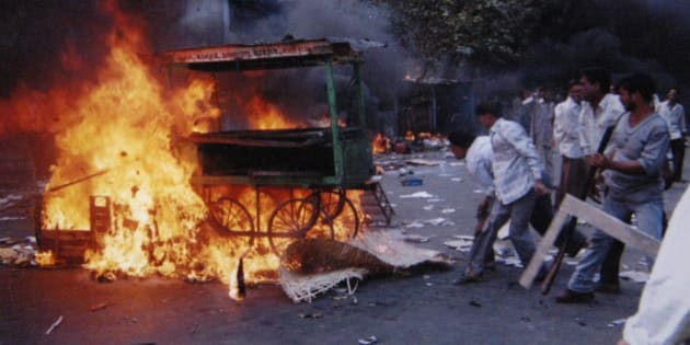 ** FILE ** A mob sets fire to vehicles and other goods in the Khokhara area in Ahmadabad, India, in this Feb. 28, 2002 file photo photo. Sectarian violence erupted as retaliation after 59 Hindus were killed when a train car burst into flames in Godhra, a town in Gujarat. In the narrow alleys where Muslim families cowered from a murderous Hindu mob, the survivors still fear one man above all others.  Narendra Modi's bearded face stares from street corners, T-shirts, key chains and mugs in this western Indian city, where he's in the midst of a grueling re-election campaign for the top post in the state of Gujarat.  The first round of voting begins Tuesday, Dec. 11, 2007. (AP Photo/Ajit Solanki, File)