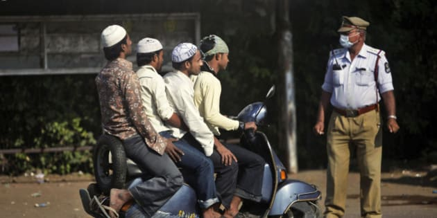 An Indian police officer controls traffic as Muslim men arrive in a scooter to offer prayers on Eid al-Adha in Hyderabad, India, Monday, Nov. 7, 2011. (AP Photo/Mahesh Kumar A.)