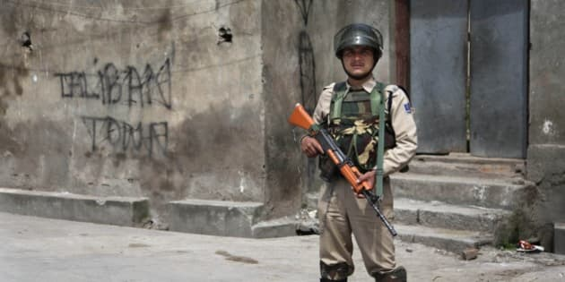 An Indian paramilitary soldier stands guard on a street during curfew in Srinagar, India, Friday, May 2, 2014. Parts of Indian-controlled Kashmir remained under curfew Friday, on the second consecutive day while general strikes were being staged in other areas after government forces fatally shot a man during an anti-India protest. (AP Photo/Dar Yasin)
