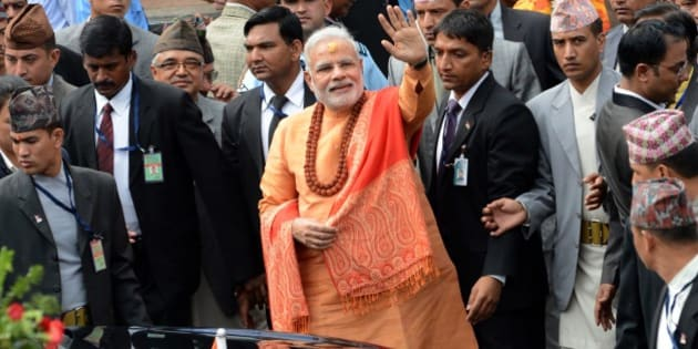 Indian Prime Minister Narendra Modi (C) waves to well-wishers as he leaves following his visit at the Pashupatinath Temple in Kathmandu on August 4, 2014.  Indian Prime Minister Narendra Modi arrived in Nepal to try to speed up progress on power agreements while also aiming to counter rival giant China's influence in the region. Modi flew into Kathmandu for talks on strengthening trade ties including harnessing Nepal's vast hydropower resources in the first visit by an Indian prime minister to the Himalayan nation in 17 years.   AFP PHOTO/Prakash MATHEMA        (Photo credit should read PRAKASH MATHEMA/AFP/Getty Images)
