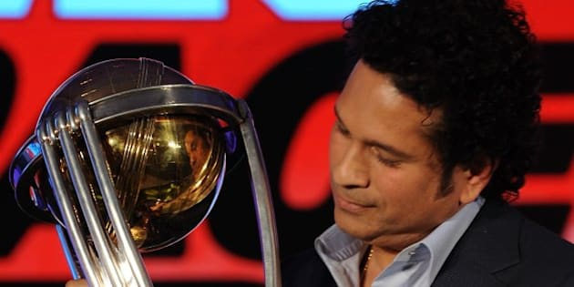 Former Indian cricketer and brand ambassador of the International Cricket Council (ICC) Cricket World Cup (CWC) 2015 Sachin Tendulkar poses for a photograph with the ICC CWC 2011 trophy during a promotional event in Mumbai on February 7, 2015. Australia and New Zealand are due to co-host the forthcoming Cricket World Cup event in which 49 matches will be played across 14 venues between February 14 - March 29.  AFP PHOTO / INDRANIL MUKHERJEE        (Photo credit should read INDRANIL MUKHERJEE/AFP/Getty Images)