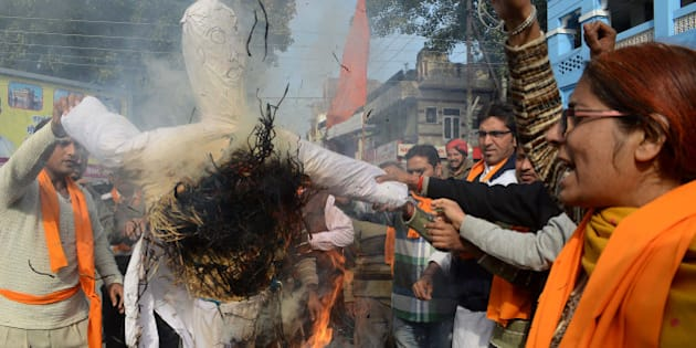Activists of Vishva Hindu Parishad (VHP), Bajrang Dal and The Durga Vahini (Army of Durga) shout slogans as they burn an effigy during a demonstration denouncing Valentine's Day in Amritsar on February 14, 2013. Hindu organizations strongly oppose Valentine's Day celebrations citing them as a cultural invasion of the conservative nation.   AFP PHOTO /NARINDER NANU        (Photo credit should read NARINDER NANU/AFP/Getty Images)